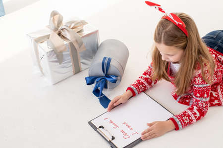 dear santa letter written by a child for Christmas.Concentrated kid is involved in the process of thinking over all her wishes and desires. Pretty Girl hold clipboard and paper near gift box.