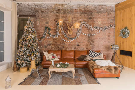Winter home decor. Christmas tree in loft interior against brick wall. Old vintage furniture.Loft apartments, brick wall with and big Christmas tree.New Year celebration at family home