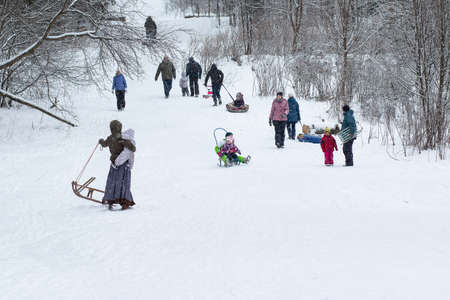 December 2, 2020. Omsk,Russia.People walk in snowy winter forest with their families, with skis, sleds, inflatable tubing, roll down hill, build snowman. Winter outdoor activities.Winter fun
