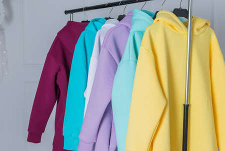 Multicolored hoodies on hangers in a sports store close up, clothing concept. Row of different hoodie ,long sleeve shirts , sweater on hangers.Modern show room selling clothes men, women children.