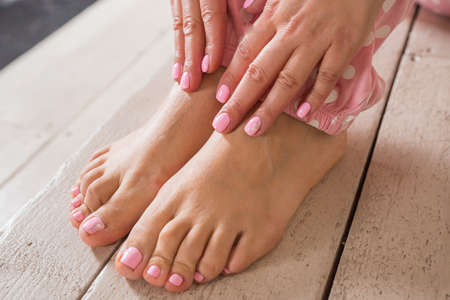 Nail spa procedure. Manicure and pedicure. Female hands and feet on wooden background. Result of spa salon procedure.Body care, spa treatments. Nail polish and Accessories. Stylish Woman. Banco de Imagens