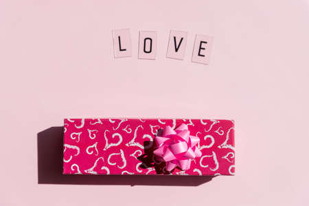 Red present box with bow. Wedding, birthday or Valentines day concept.Love text with black letters on pink background. Greeting card.Copy space.congratulation. invitation.Word Love, Creative card