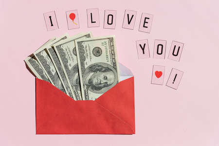 open a paper envelope with the hundred dollar bills, isolated on pink background.Banknotes folded in an envelope as a present. Sending or saving money, corruption concept.Cash bills for gifts