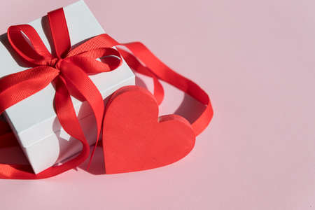 white Gift box with red bow ribbon and red heart on pink background for Valentines day.Happy birthday, wedding, greeting card, love symbol.display of feelings
