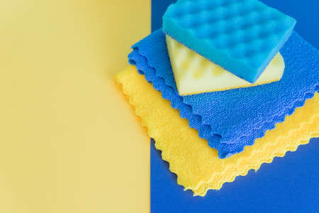composition with dishwashing sponges and microfiber rags on blue background, copy space. Home Care Concept.Detergents and cleaning accessories. Cleaning service concept.Washing,cleaning equipment.