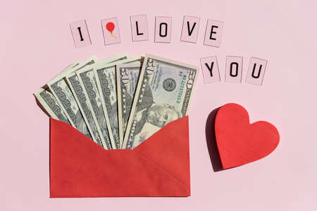 Red paper envelope with dollar bills and red heart isolated on pink background.Banknotes folded in an envelope as a present. Sending or saving money, corruption concept.Medicine and money