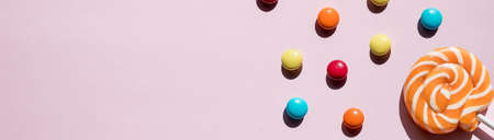 Pink candies, lollipops and jelly beans on pink background. Sweet greeting card. pastry shop. Top view.Romantic sweets. Candies and jelly beans for Valentines Day. sweets. Web banner.Copy space