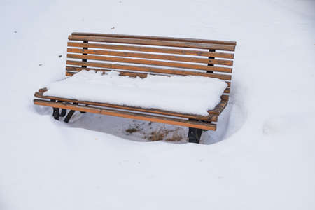 Park bench covered by heavy snow.lonely wooden bench under snow fall. snowfall day. Perfect for christmas holidays Banco de Imagens