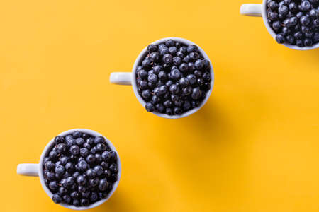Creative pattern of blueberries in white cups on bright background.Seamless pattern Cup of berries. Fresh sweet fruits. Food background. Summer snack.raw organic blueberry in a mug Banco de Imagens
