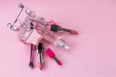 Makeup in pushcart isolated on pink background.Miniature shopping trolley cart with a set of cosmetics.For web design, postcard, banner. Buying cosmetic, online shopping concept.Copy space.