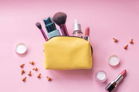make up bag with cosmetics and brushes isolated on pink background. Yellow bag with cosmetics.Basic colors pink and gold. skin cream, lipstick, handbag, vanity case, brush.cosmetic goods Banco de Imagens