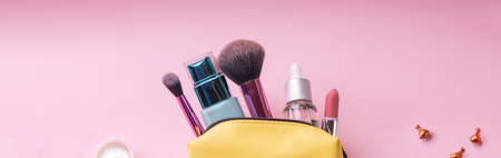 make up bag with cosmetics and brushes isolated on pink background. Yellow bag with cosmetics.Basic colors pink and gold. skin cream, lipstick, handbag, vanity case, brush.cosmetic goods.Web banner