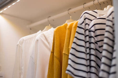 Many blouses,shirts on hangers in the dressing room.Modern wardrobe with stylish spring clothes and accessories.Rack with different clothes in a shop or home closet Stock Photo