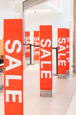 Inscription Sale on the background of a red glass wall in the store. Mall Discount Announcement. Summer, winter Christmas, New Year sale