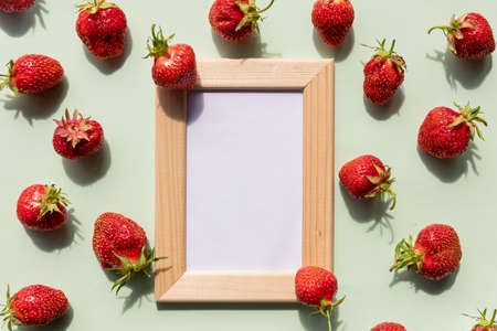wooden picture photo frame mockup with copy space.red fresh summer berries on soft green backgound.mock up for design, summer mood, sale banner.natural berries, not genetically modified products Imagens