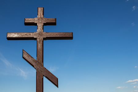 double cross: Wooden symbol: double cross. Blue sky in the background, several small white clouds. Stock Photo