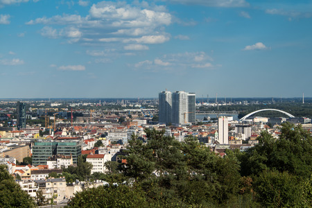 river scape: View on the capital of Slovakia, Bratislava. Center of the city, with skyscrapers, bridge and factory in the background. Blue sky with white clouds.