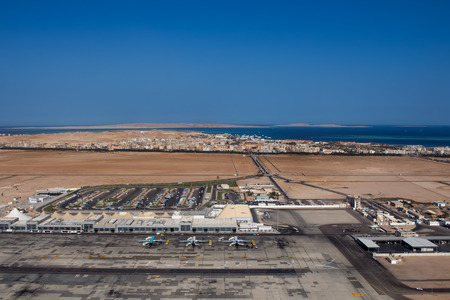 hurghada: View on the buildings of the international airport in Hurghada, Egypt. City in the background together with sea. Blue clear summer sky. Stock Photo