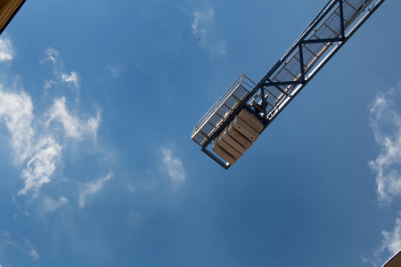 overhead crane: Detail of a crane with a background of a bright blue sky with small clouds. Stock Photo