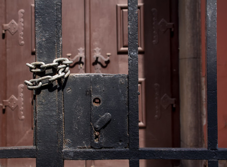 keep gate closed: Grid fence with a missing handle. Twisted chain to keep it closed. Massive wooden decorated gate in the background.