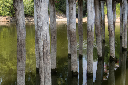 bole: Detail of the construction of a wooden bridge across a small river. Green water, riverbanks in the background.