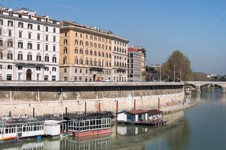 embankment: Embankment of Tiber with residential houses. Boats on the river. Bridge in the background. Summer blue sky. Stock Photo