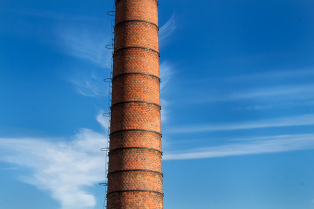phallic: Factory high chimney, made of bricks. Blue sky in the background, with a twist of clouds around the chimney.