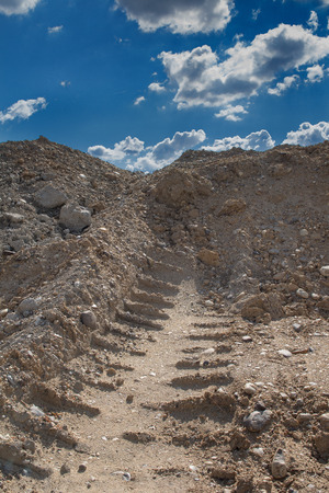 Sandy soil: Camino a la colina con un rastro. El suelo arenoso con un mont�n de piedras. Cielo azul con muchas nubes contraste.