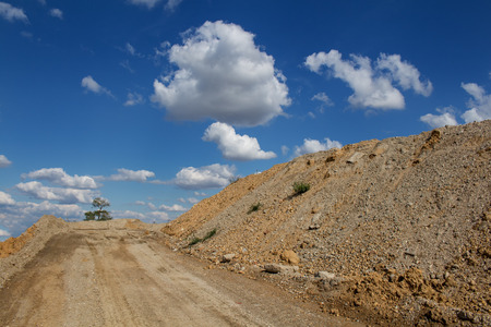 devastated: Road up the hill. Place ready for building. Devastated nature, just one tree remaining. Dry hill on the right side. Blue sky with many clouds.