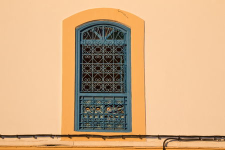 Contrast of the yellow facade with the traditional grating of the window. Stock Photo