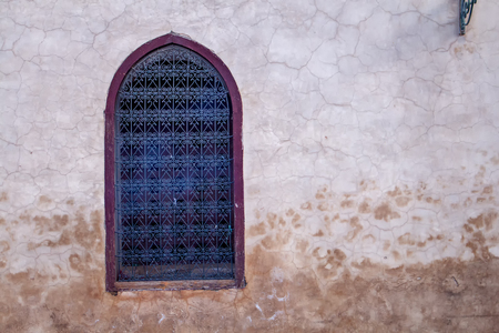 windows: Old wall with a window with ornamental grating. Contrast frame around the window. Stock Photo