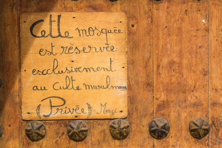 informing: Small board on a gate to a mosque in Marrakesh, informing its reserved just for muslims. Written in French language.