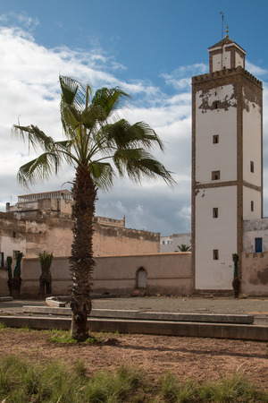 madina: Minaret of an old mosque in Essaouira and a palm tree. Cloudy sky.