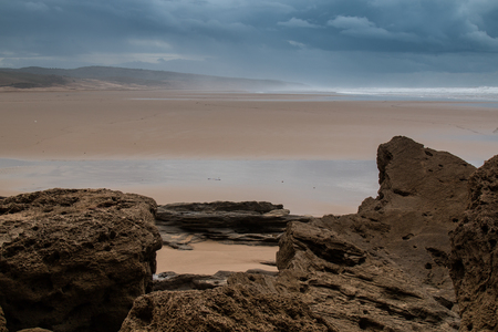 Cloudy day on a sandy beach of Atlantic Ocean in Morocco. Big rocks in the foreground.