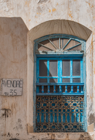 diagonally: Blue framed window with traditional arabian details and wall of the house for sale. Diagonally divided with a shadow.