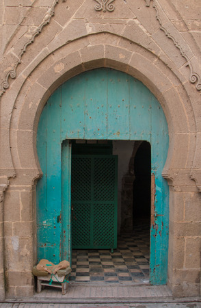 islam: Stone frame of the gate in traditional style, green opened door. Stock Photo