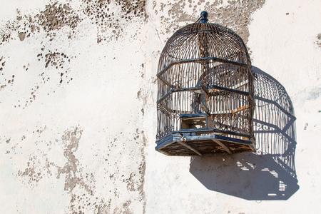Vide élégante cage d'oiseau suspendu sur le vieux mur.