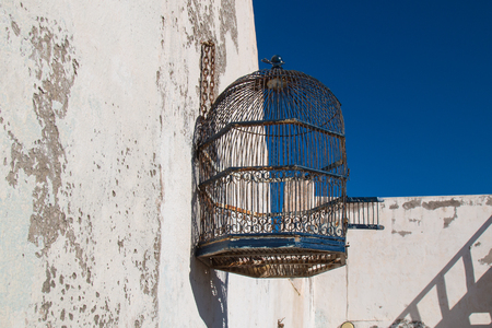 liberated: Empty stylish bird cage hanging on the old wall. Bright blue sky.