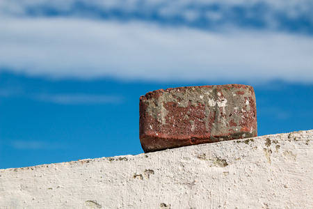 wall clouds: Old brick on the edge of the wall. Bright blue sky with many clouds in the background.