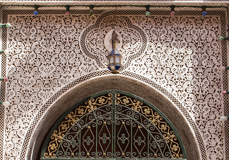 Rich decoration of the gate in Marrakesh. Traditional pattern made in a stone. Marrakesh, Morocco.