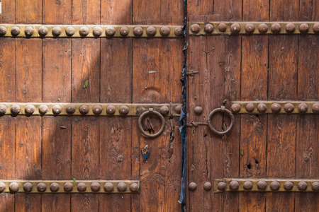 Old wooden gate with iron details, partly enlightened by the sun. Marrakesh, Morocco Stock Photo