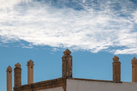 chimney corner: Corner of a roof with many traditional chimneys. Cloudy sky. Essaouira, Morocco.