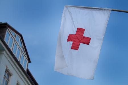 cielo de la tarde temprano en el fondo de una bandera de la Cruz Roja.