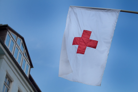 Early evening sky in the background of a Red Cross flag.