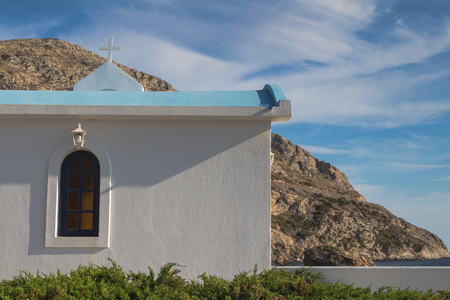 christian religion: White traditional greek church surrounded by mountains from one side and a sea from another side. Blue sky with many white clouds.