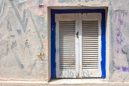 vandalize: Blue framed window with white closed shutter. Wall of the house with partly covered graffiti. Plaka, Athens, Greece. Stock Photo