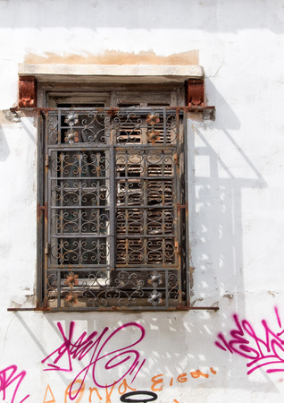 lattice window: Old destroyed window with ornate lattice. White facade of the house with graffiti. Athens. Greece.