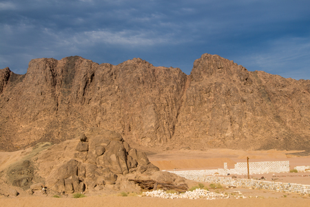 egyptology: Golden hour in the mountains on the desert in Egypt. Later afternoon dark blue sky with some clouds.