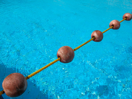 floater: Diagonal line of the buoys on the rope, dividing the swimming pool. Fresh bright blue color of the water with small waves in the windy weather.