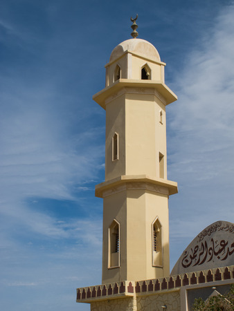 mohammedan: Light yellow color of the facade of a mosque in Egypt. Details of the tower. Blue sky with intense white clouds. Stock Photo